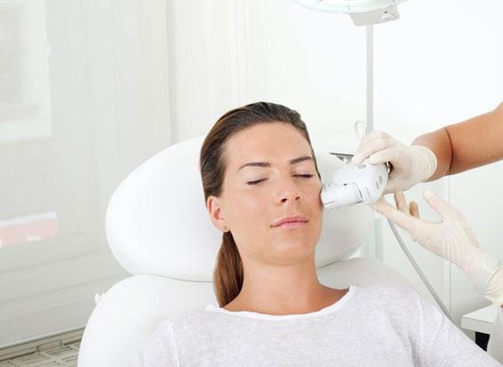Strahlung des Gesichts mit Ultherapy: Attraktive Frau während der Behandlung.