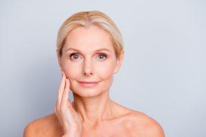 Strahlende Frau zufrieden mit ihrem Gesicht. So fühl sich die Ergebnisse eine Strahlung der Kinnpartie mit Ultherapy an!
