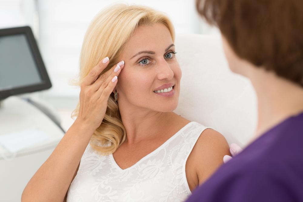 Straffung der Augenpartie mit Ultherapy: Strahlende Frau zeigt auf die betroffene Stelle.