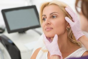Straffung der Augenpartie mit Ultherapy: Attraktive Frau bei der Untersuchung der Ergebnisse.