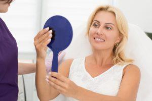 Perfekte Haut mit Ultherapy: Attraktive Frau sieht das Ergebnis der Straffung der Augenpartie im Spiegel.
