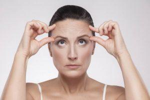 Hautstraffung mit Ultherapy: Attraktive Frau zeigt auf kleine Falten im Gesicht.