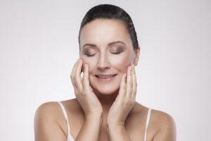 Attraktive Frau zufrieden mit ihrem perfekten Gesicht. So gut fühlt sich eine Hautstraffung mit Ultherapy an.
