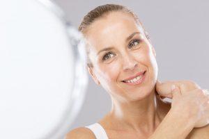 Strahlende Frau zufrieden mit ihrem perfekten Halspartie. So gut fühlt sich eine Halsstraffung mit Ultherapy an.